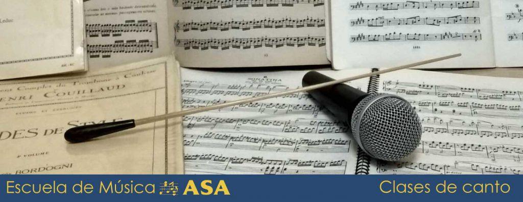 Batuta y micro sobre partituras, elementos de la clases de canto